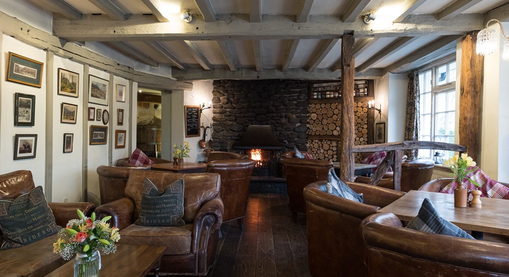 Cosy leather seats and log fire in the lounge at The Wild Boar