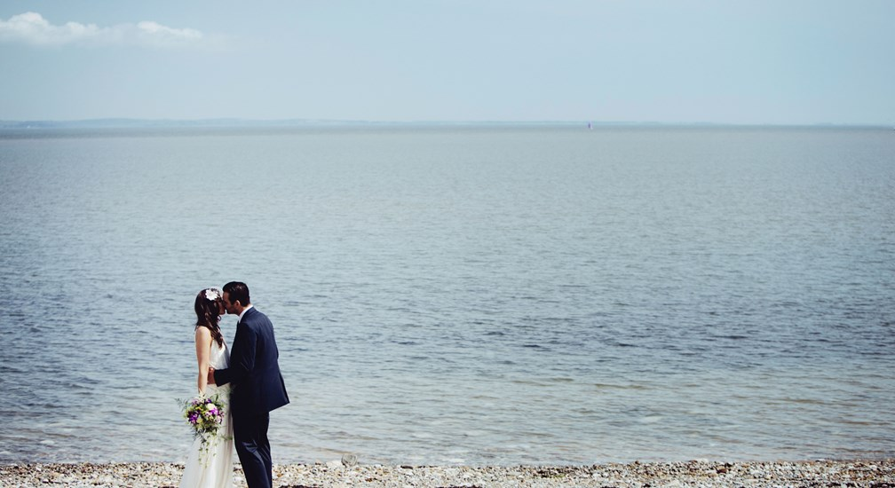 Couple posed for Wedding Photography on the beach in-front of The Midland