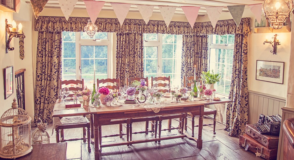 Head table bedecked with flowers and bunting - Weddings at The Wild Boar