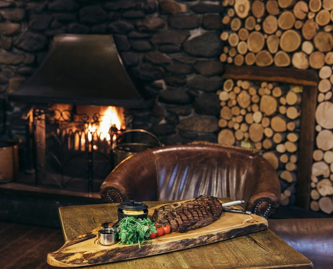 Enjoy steak by a cosy fireside table in the lounge - The Wild Boar
