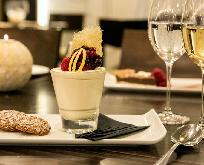 White mousse with red berry fruits and spun caramel and 2 glasses white wine