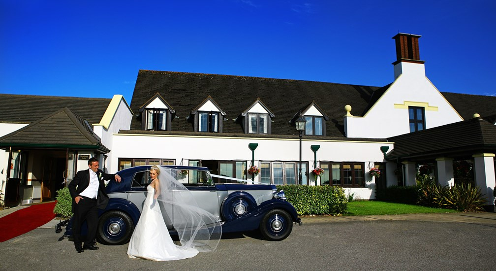 Couple stood by a classic car posed for the wedding photographer at Lancaster House Hotel