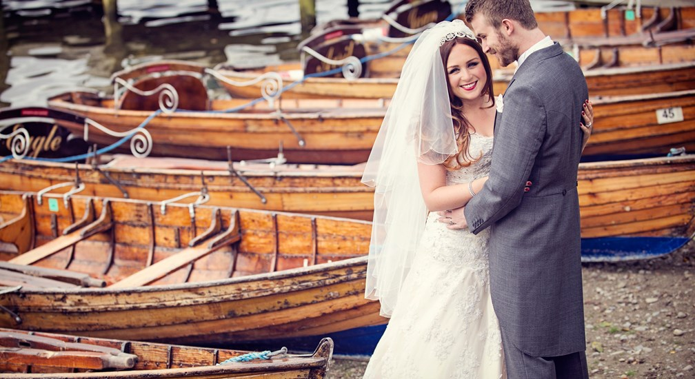 Couple posed for wedding photos by the rowing boats at Waterhead