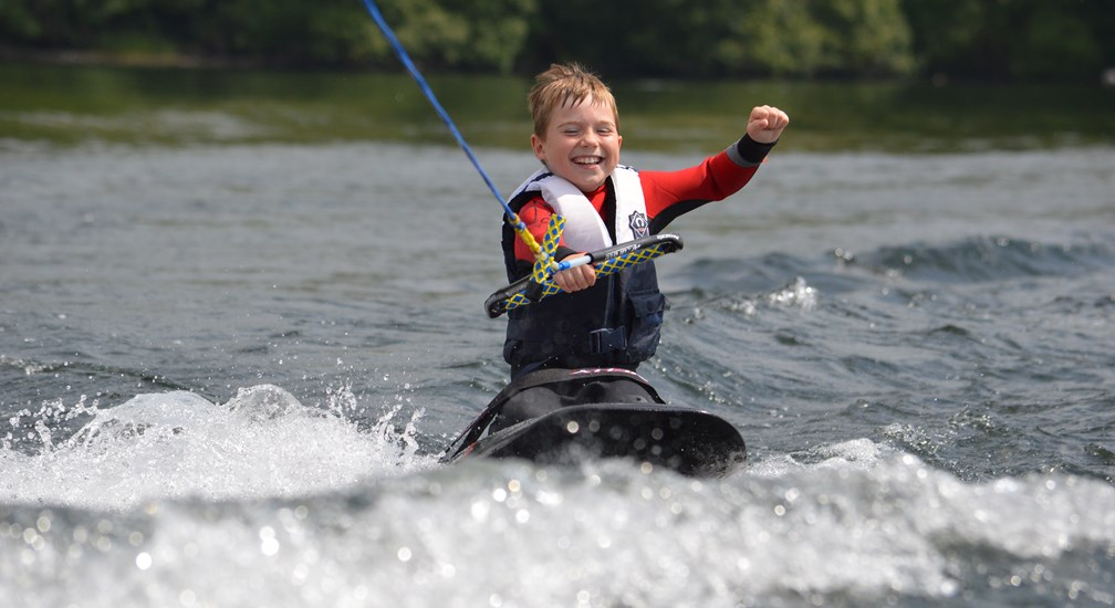 A child wakeboarding on Lake Windermere
