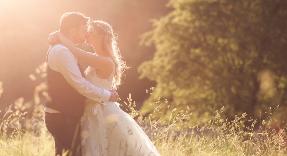 Newly Weds kissing in the hazy sun of the The Wild Boar woods