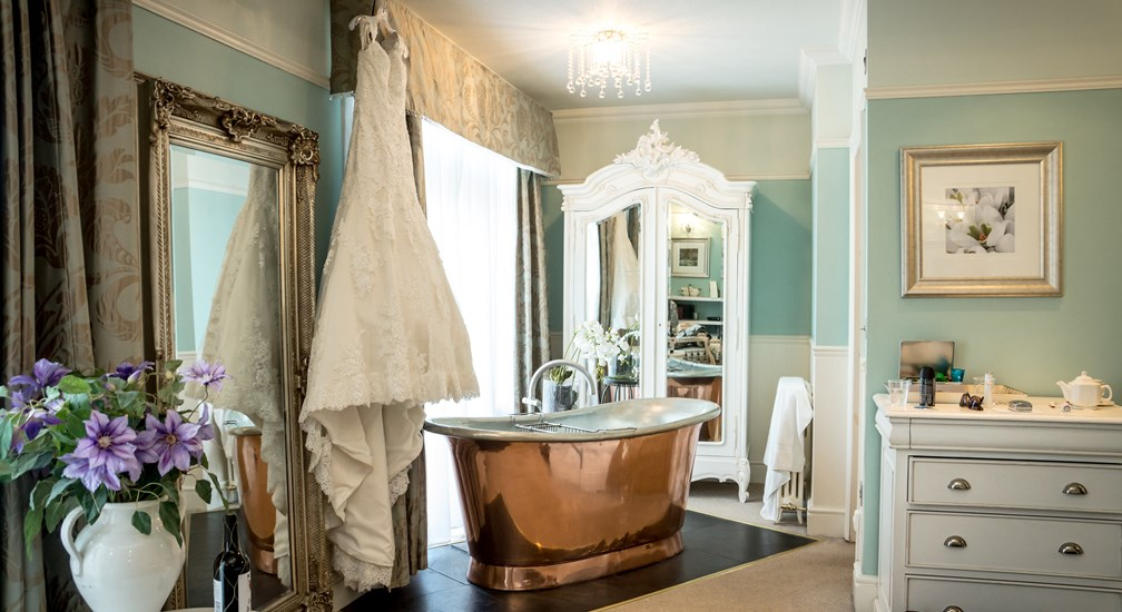 Hotel bedroom with copper bath and wedding dress at The Wild Boar