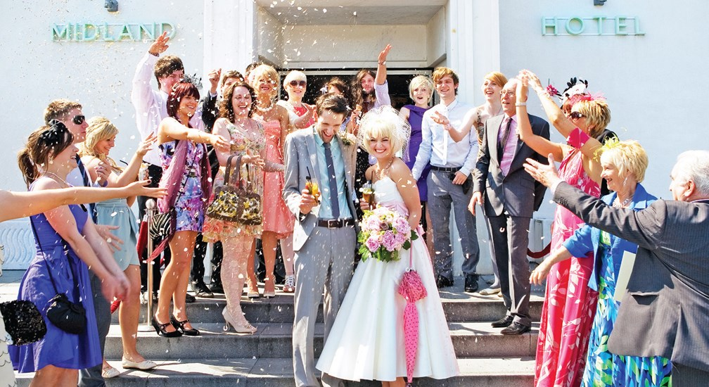 Wedding guests casting confetti on the Bride & Groom on The Midland Hotel entrance