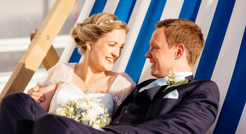 The Bride & Groom sat on the large striped deckchair at The Midland