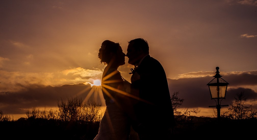 Couple silhouetted by the setting sun on their Wedding Day at Lancaster House Hotel