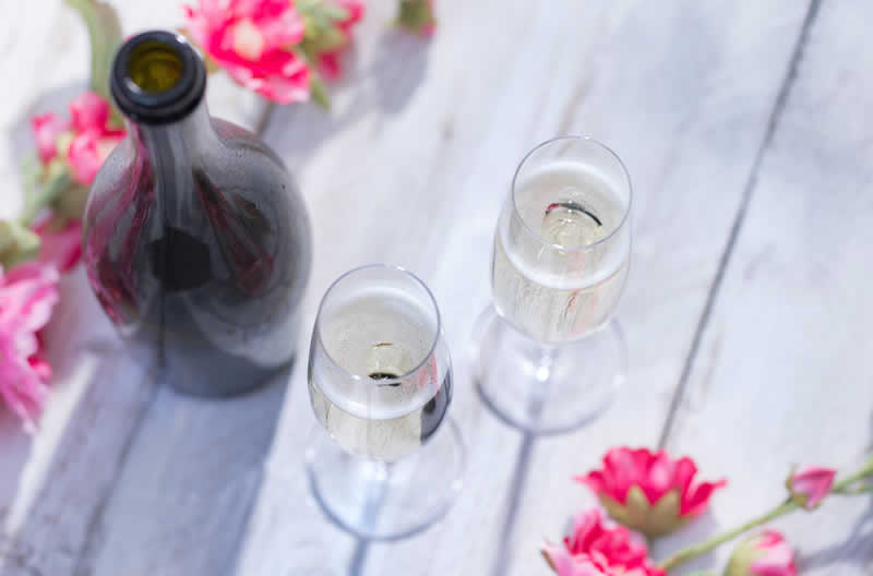 Bottle of Prossecco with 2 glasses and a scattering of pink flowers