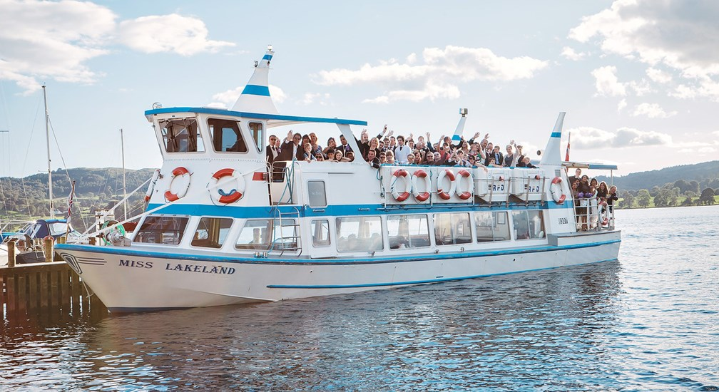 Wedding Party waving from Windermere Lake Cruises Boat on Low Wood Bay jetty
