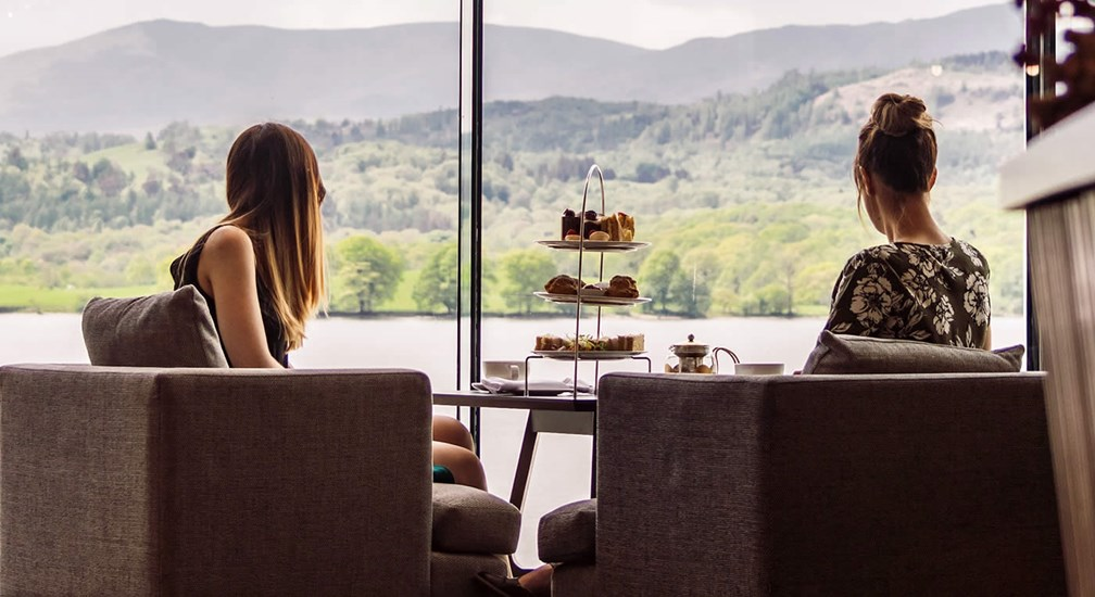 Couple sat in the picture window with afternoon tea