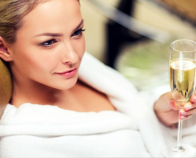 Young woman in white dressing gown with a flute of champagne