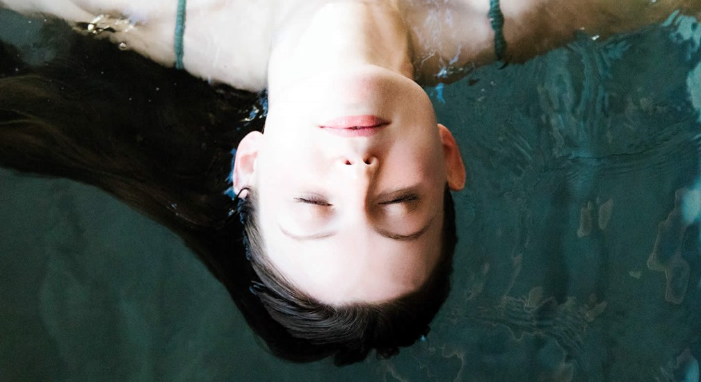 A young woman floating on her back in the water
